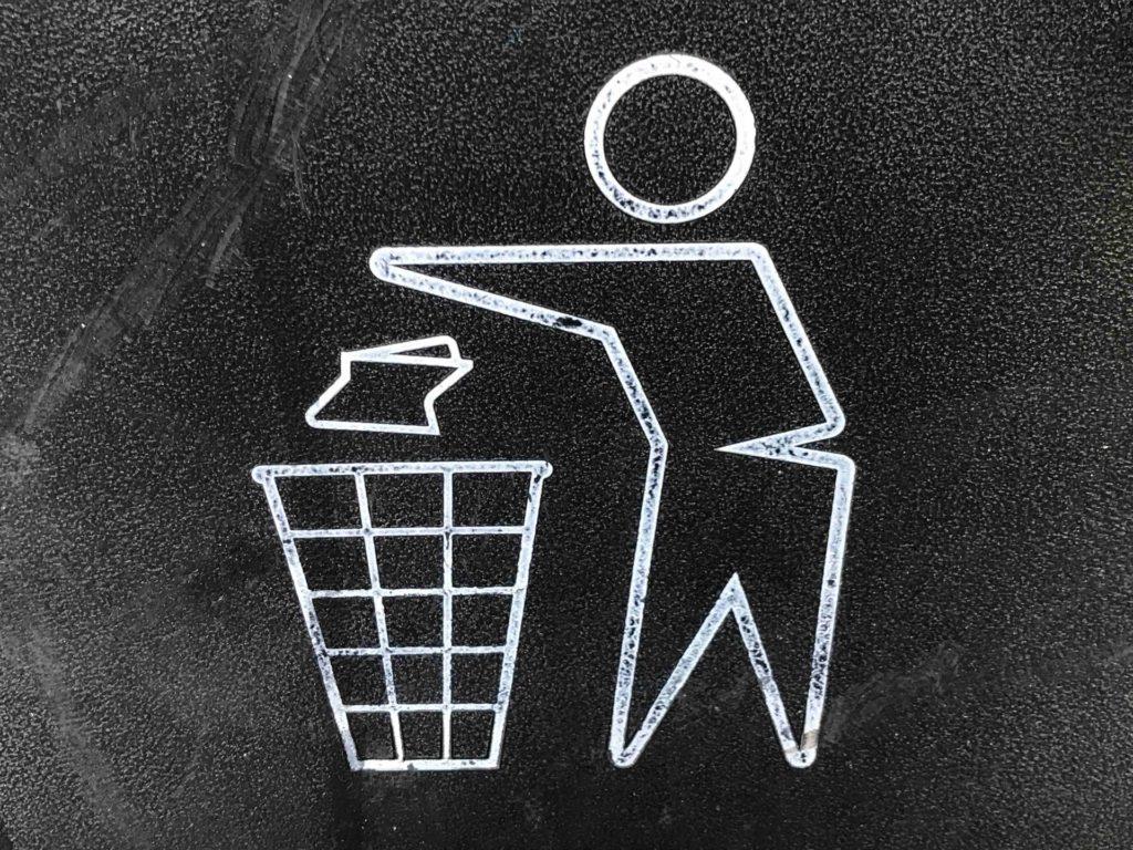 Imagem mostra um desenho de uma pessoa jogando lixo no lixo