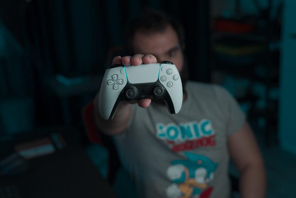 Gamer exibindo o controle de um playstation 5
